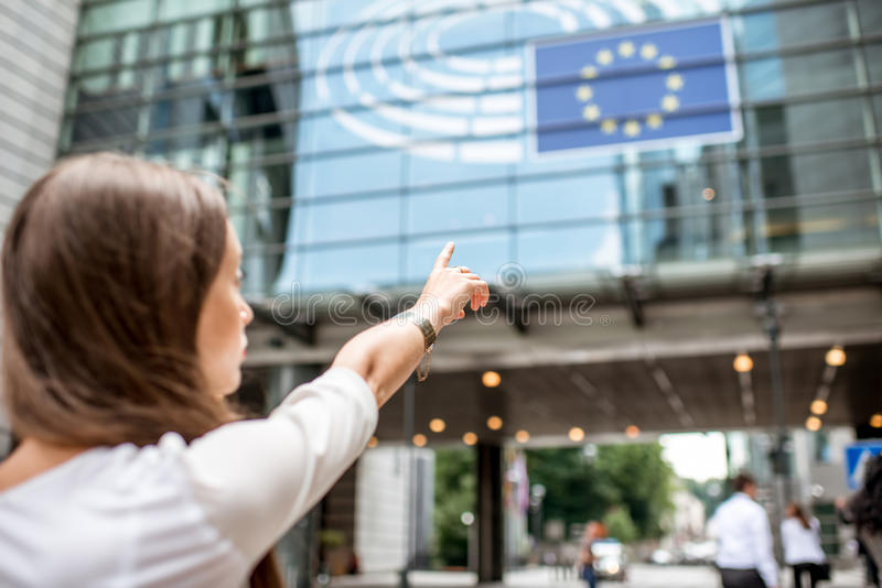 Woman pointing on the european flag. Woman pointing with hand on the european flag on the parliament building in Brussel royalty free stock images