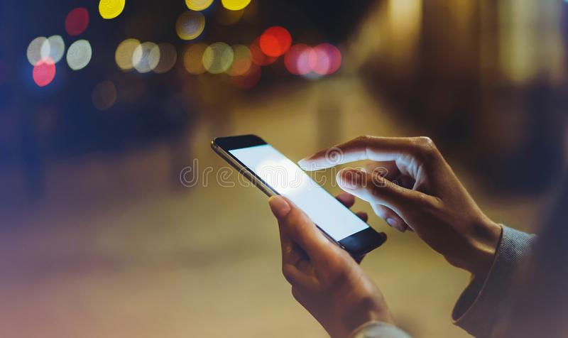 Woman pointing finger on blank screen smartphone on background bokeh light in night atmospheric city, blogger hipster using in han royalty free stock photos