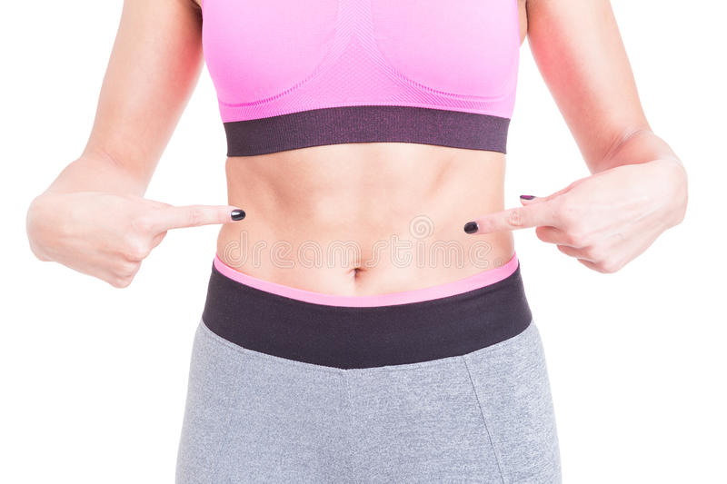 Woman pointing her flat tummy or abs royalty free stock photo