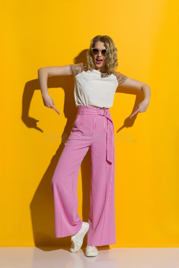 Woman Is Pointing At Her Striped Wide Legs Trousers And Talking. Young woman in sunglasses is pointing at her striped wide legs trousers snd talking. Full length royalty free stock photography