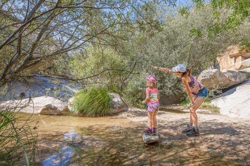 Woman pointing nature to her daughter in a river of Camorza Gorge near Madrid royalty free stock photography