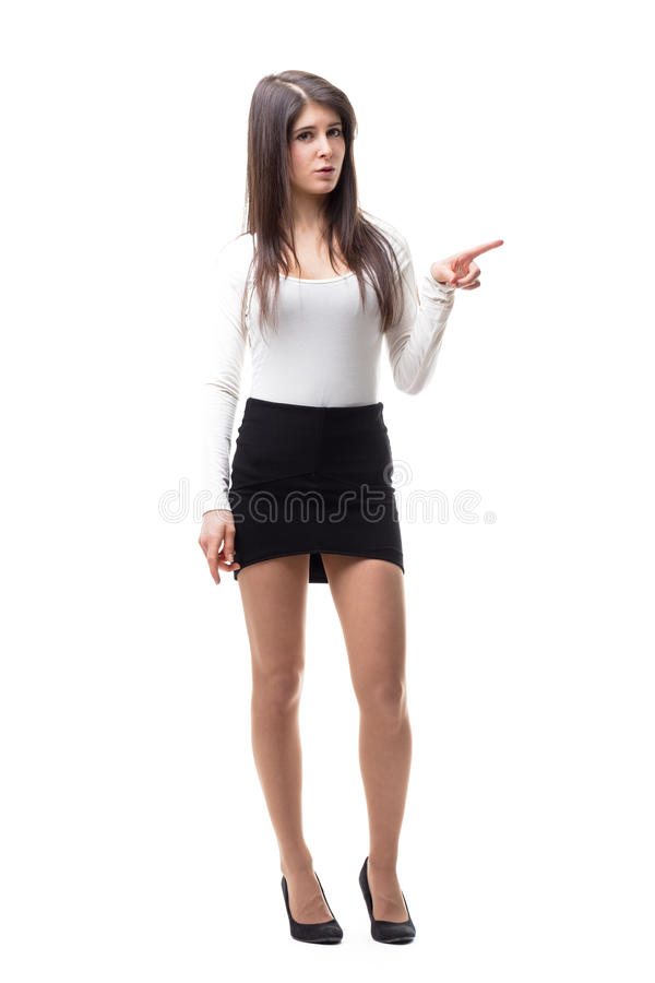 Woman pointing out her left finger. Isolated on white, long haired woman with a short skirt and white sweaterand long legs on high heels pointing out her finger royalty free stock photography