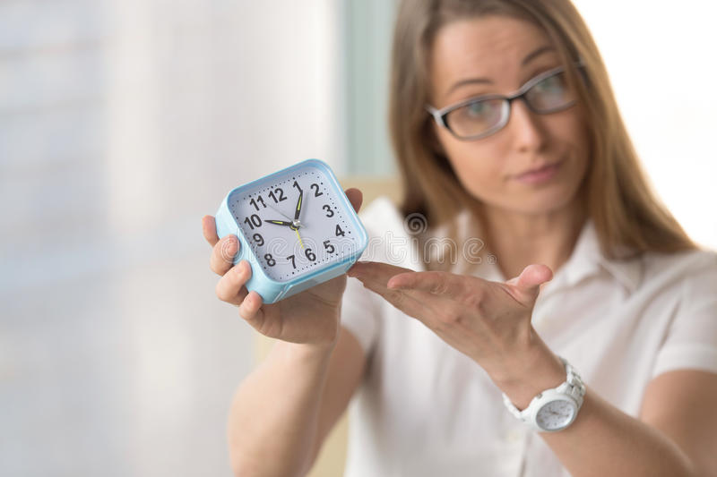 Woman pointing at time, focus on clock, deadline punctuality con. Waiting woman pointing at time, urging to hurry, warning not being late or miss appointment stock image