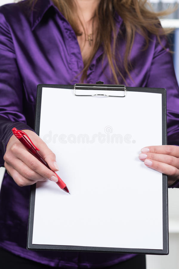 Woman is pointing to a clipboard with a pen royalty free stock photos
