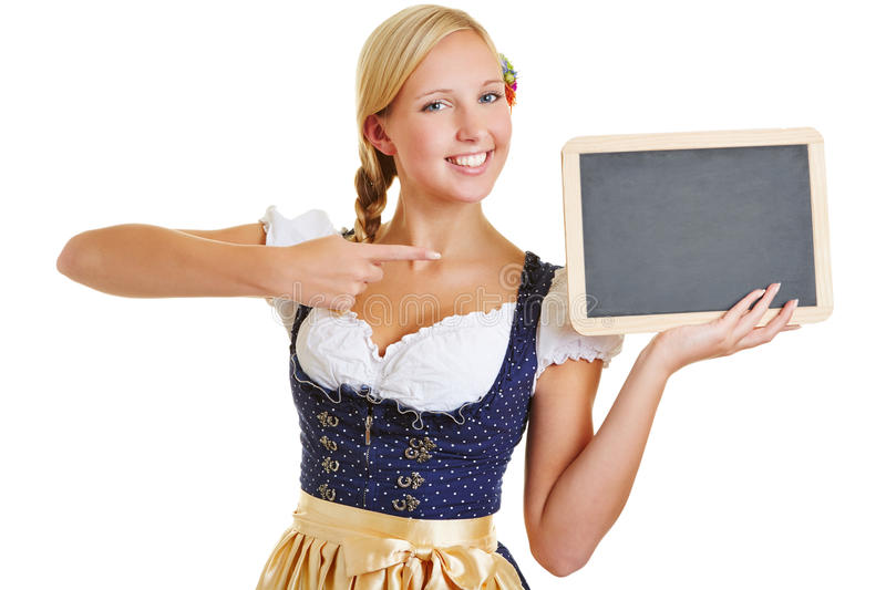 Woman pointing to empty blackboard. Happy young woman in a dirndl pointing with her index finger to empty blackboard stock images