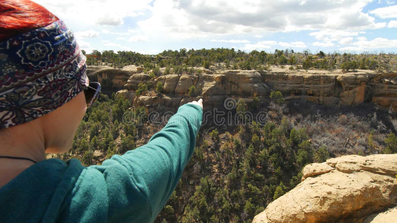 Woman Points out Ancient Ruins Across Canyon royalty free stock photos