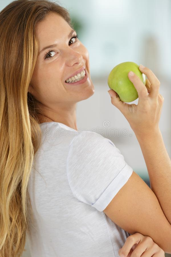 Woman poised to eat ripe green apple stock photos