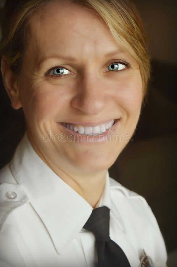 Woman Police Officer. A portrait of a lady police officer in her dress shirt and tie smiling stock image