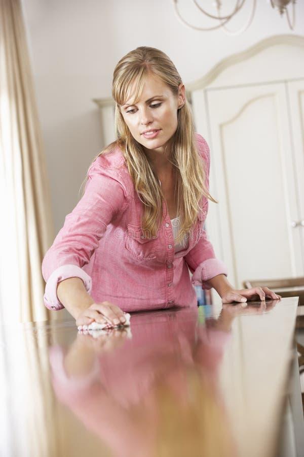 Woman Polishing Table At Home royalty free stock image