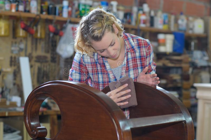 Woman polishing wooden object in workshop stock images