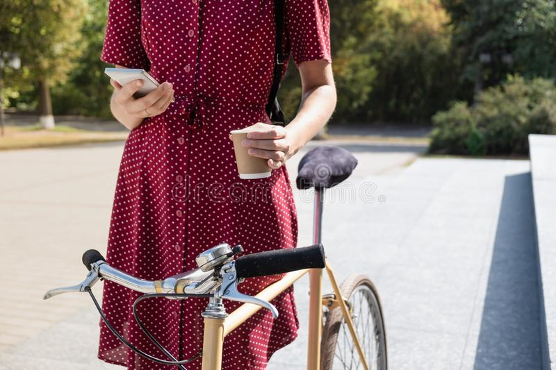 Woman in polka dot dress with bike commuting, checking mail onl stock photography