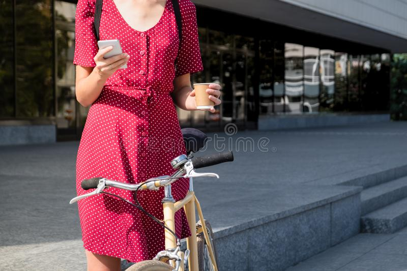 Woman in polka dot dress with bike commuting, checking mail onl royalty free stock image