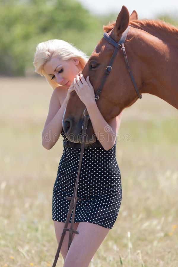 Woman in polka-dot dress with brown horse. Blonde woman stroking gelding. Young blonde woman in polka-dot dress with brown horse royalty free stock images