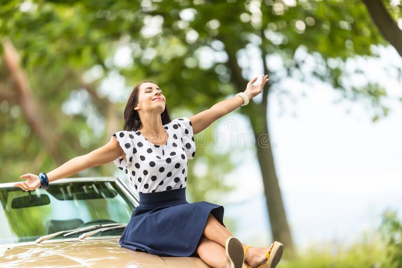 Woman in polkadot blouse and skirt sits on a bonnet of a cabrio car, arms open, enjoying summer stock photos
