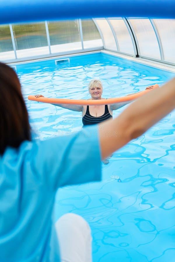 Woman in the pool doing water aerobics. Senior women in the pool doing water aerobics under guidance stock image