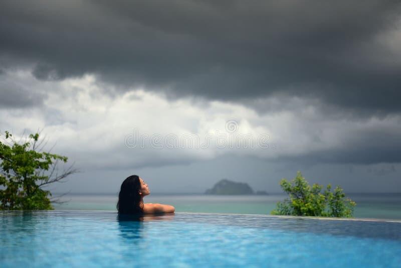 WOMAN IN POOL OVER OCEAN UNDER DARK STORM CLOUDS stock image