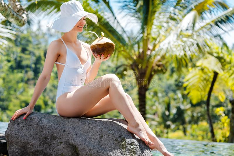 Woman on poolside with coconut relaxing in the holidays royalty free stock photography