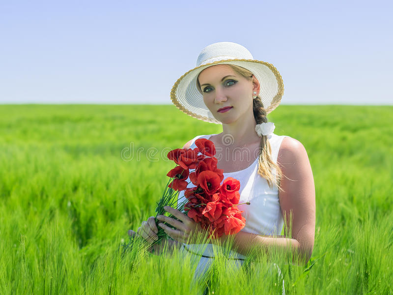 Woman with poppy flowers in field of green rye. royalty free stock photography