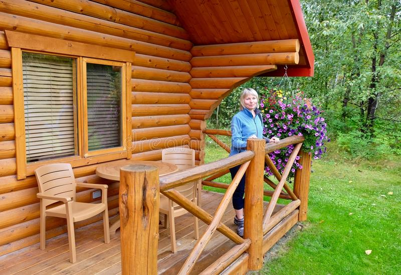 Woman on porch of vacation rental wooden cabin. stock photography