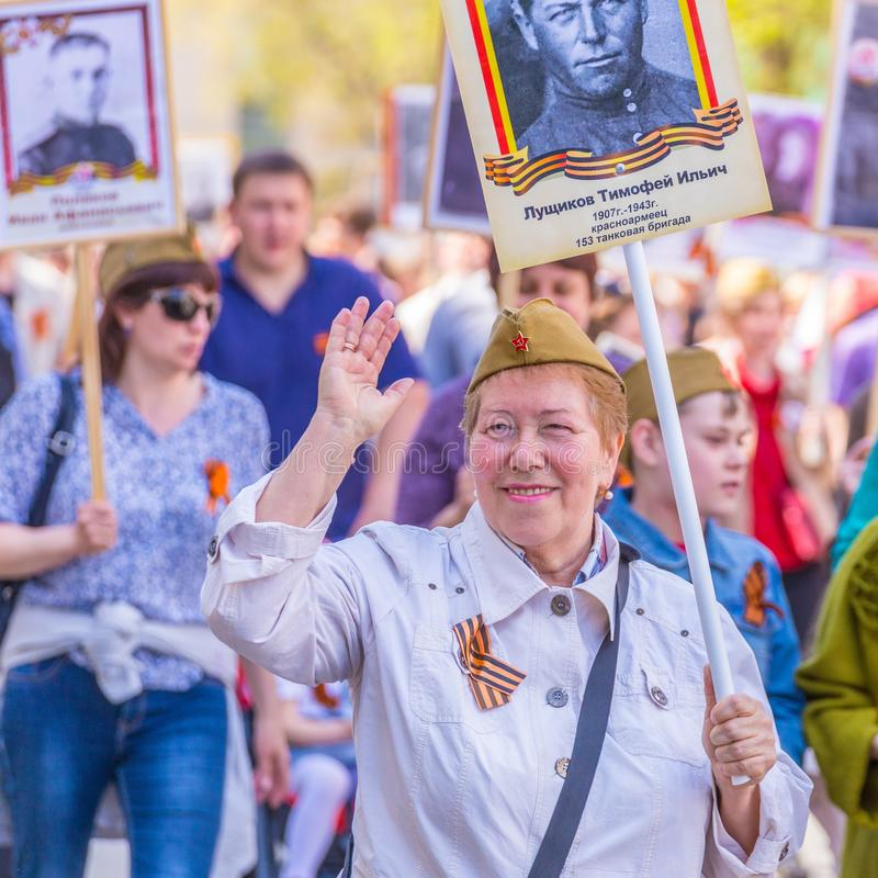 A woman with a portrait of an ancestor of a participant in the Great Patriotic War is walking along the column `Immortal Regiment. Russia, Samara, May 2018: A royalty free stock images