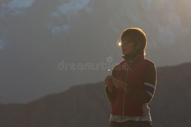 Woman portrait in backlight with sun star reflection on eyeglasses, outdoor activity, toned image. stock photos