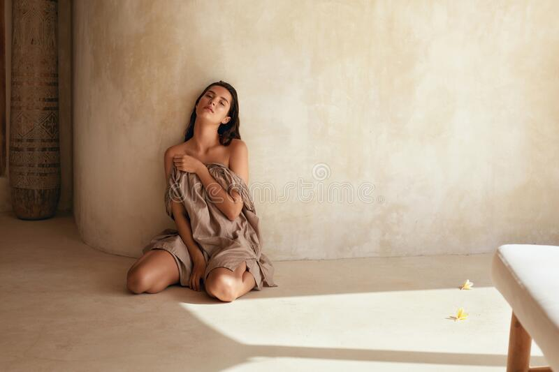 Woman. Portrait Of Beautiful Model Sitting Near Wall On Terrace. Seductive Brunette With Perfect Skin Posing On Floor. royalty free stock photo