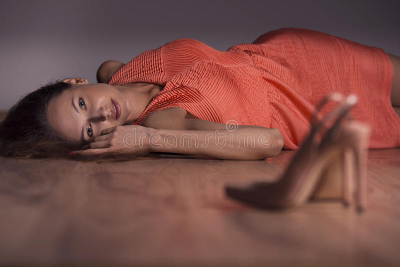 Woman. Portrait of a beautiful young woman lying on the floor in an orange dress