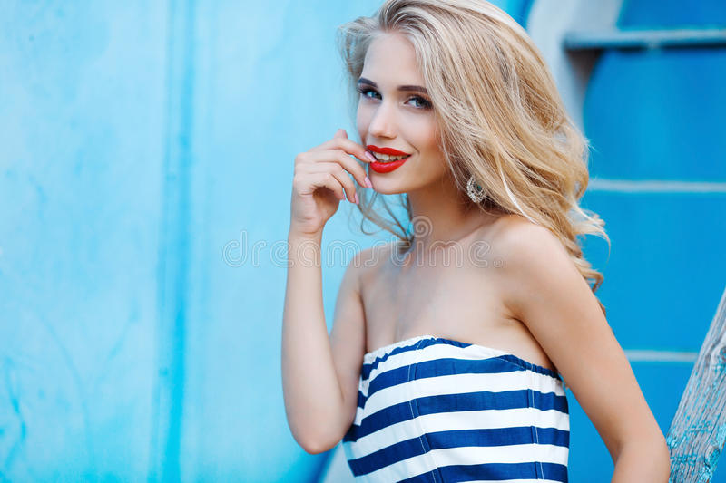 Woman portrait on blue background. Attractive young woman with long blond hair and gray eyes, dressed in a long white blue stripe dress,makeup and beautiful royalty free stock photos