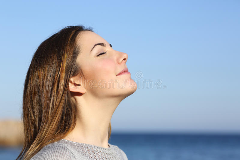Woman portrait breathing deep fresh air. Woman profile portrait breathing deep fresh air on the beach with the ocean in the background stock photos