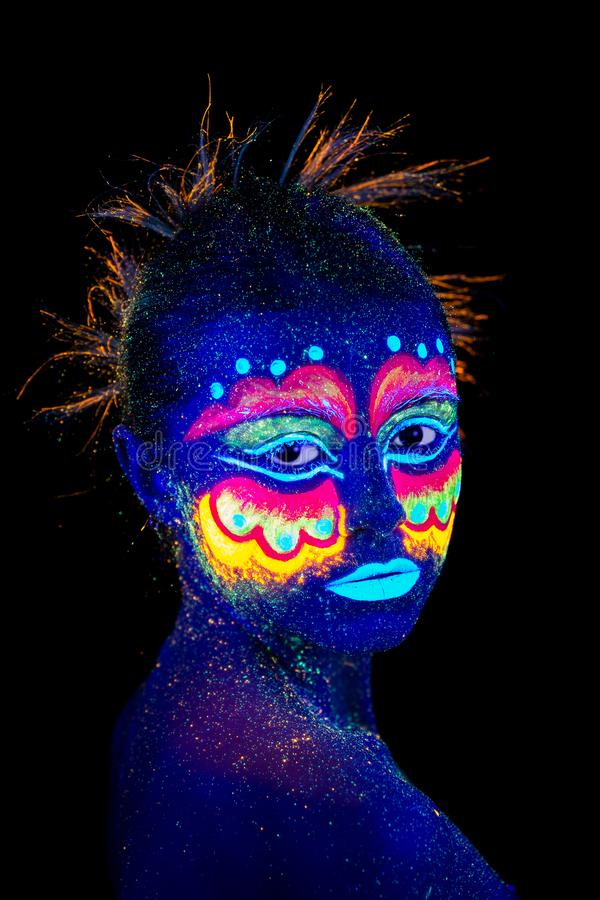 The woman portrait face, aliens portrait in semi-profile, ultraviolet make-up. Beautiful aborigine. royalty free stock photos