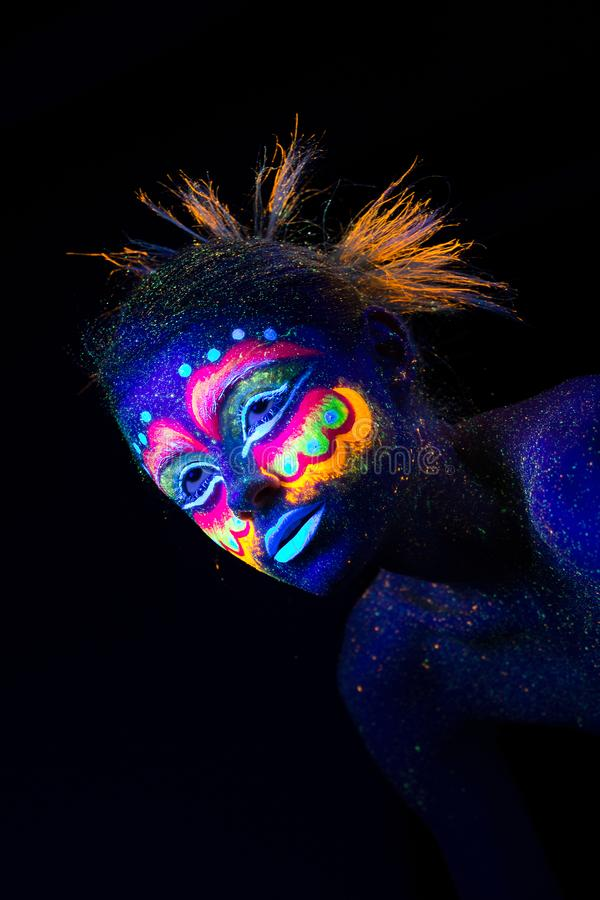 The woman portrait face, aliens portrait in semi-profile, ultraviolet make-up. royalty free stock photography