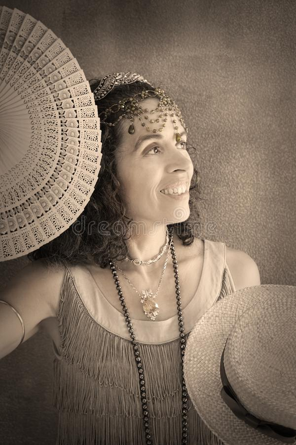 Woman portrait flapper 1920s. Portrait of a smiling woman dressed in a fringed flapper dress is holding a fan and a boater hat. She is wearing jewelry, long royalty free stock photos