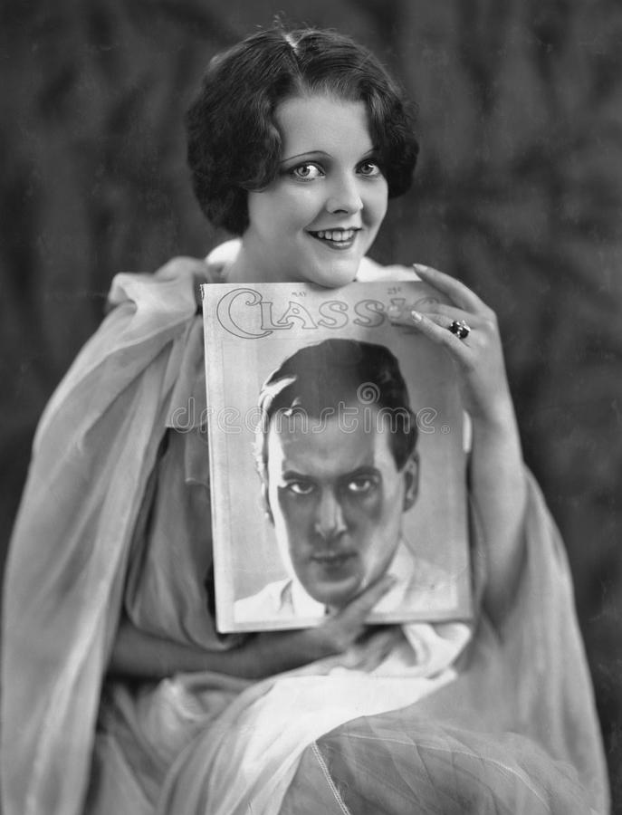 Woman with portrait of man on magazine cover royalty free stock photos