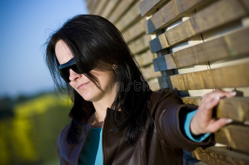 Woman portrait outdoor. Portrait of a lovely brunette woman outdoors next to a wooden slat wall stock images