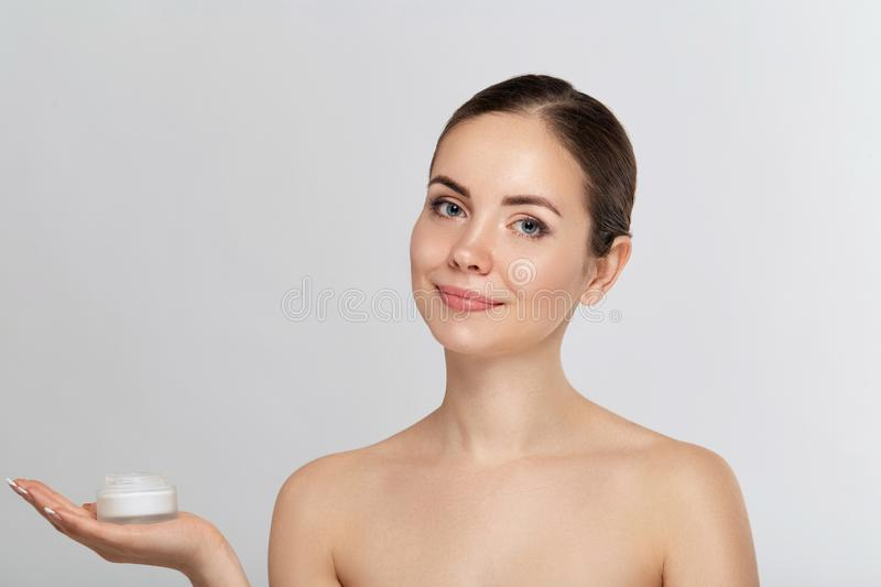 Woman portrait, skin care concept, beautiful skin and hands holdinging and apply moisturizing cream. Facial treatment. Cosmetology royalty free stock photo