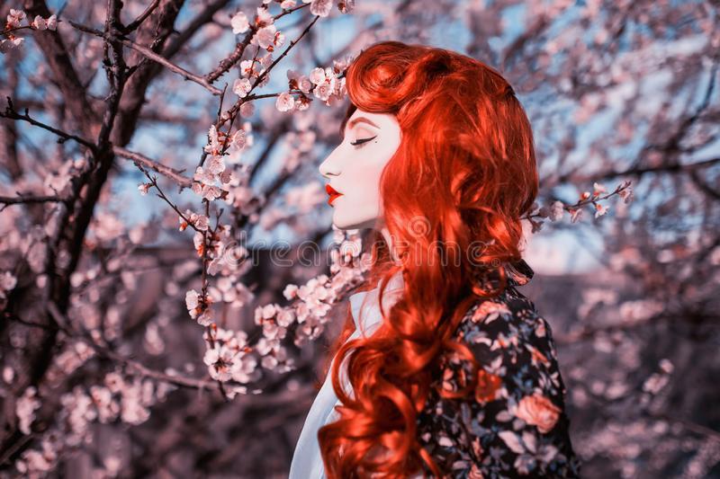 Woman portrait in spring flower garden. Valentine day background. Attractive redhead lady in dress. Woman in ribbon on nature. Background. Attractive redhead stock photo