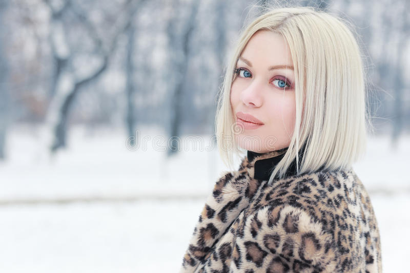 Woman portrait in winter. Young blond woman portrait in winter park weared in furry coat royalty free stock photos