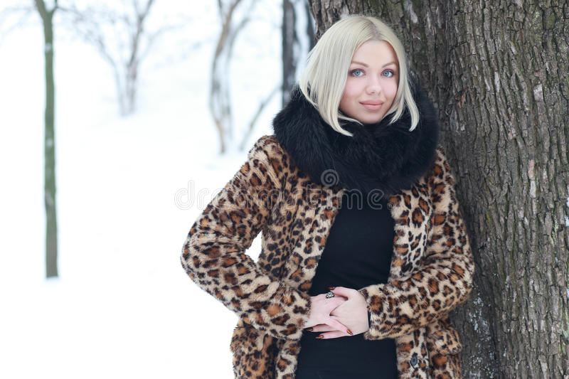 Woman portrait in winter. Young blond woman in winter park weared in furry coat stock photography