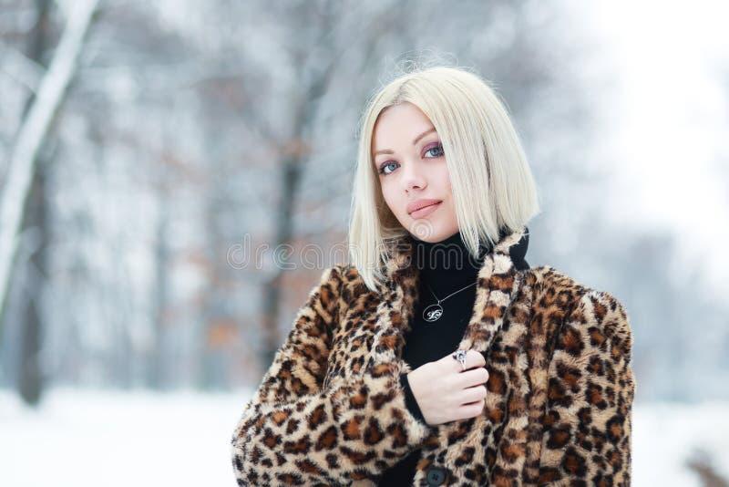 Woman portrait in winter. Young blond woman portrait in winter park weared in furry coat royalty free stock photo