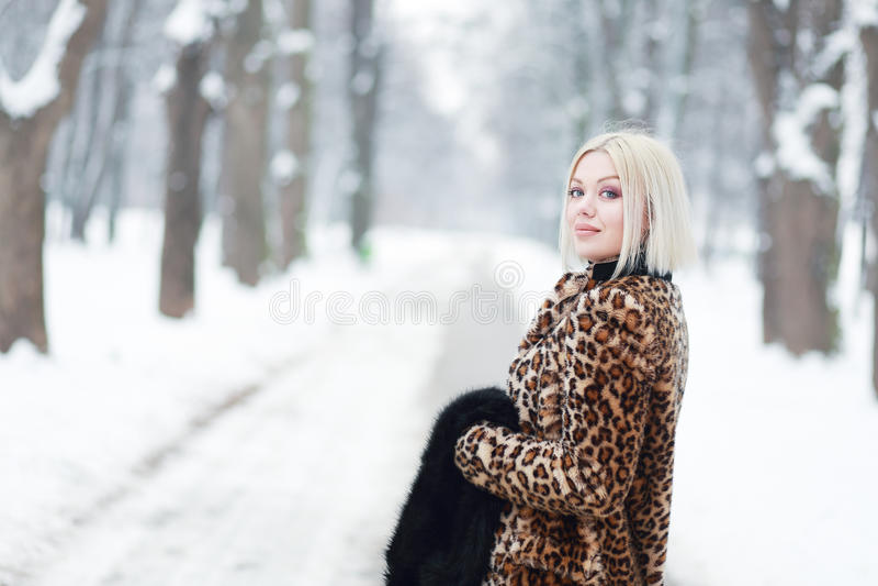 Woman portrait in winter. Young blond woman portrait in winter park weared in furry coat royalty free stock image