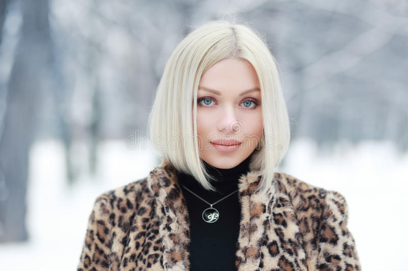 Woman portrait in winter. Young blond woman portrait in winter park weared in furry coat royalty free stock photography