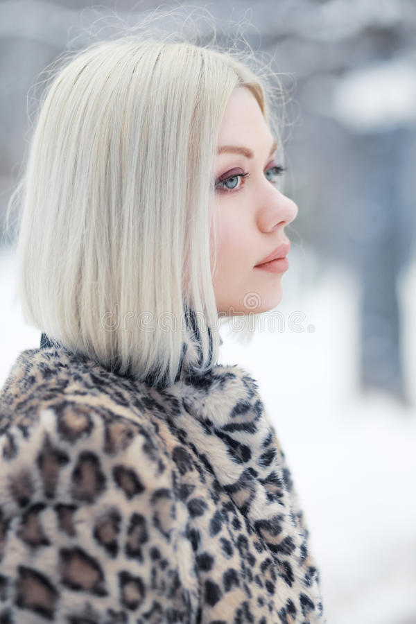 Woman portrait in winter. Young blond woman profile portrait in winter park weared in furry coat stock photography