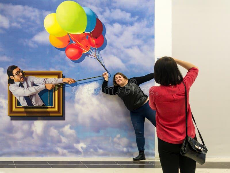 Woman Poses for a Balloon Illusion stock photo