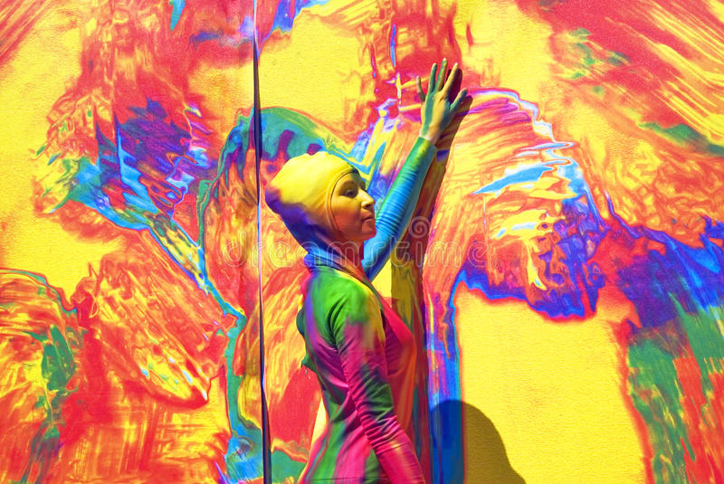 Woman poses for fotos at colorful background. SAINT-PETERSBURG, RUSSIA - JUNE 10, 2015: Portrait of a woman, her body is totally covered by paint, and she poses