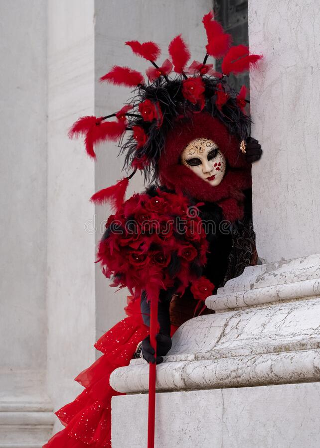 Woman poses in ornate, detailed costume, mask and hat outside San Giorgio Maggiore during Venice Carnival, Italy. stock image