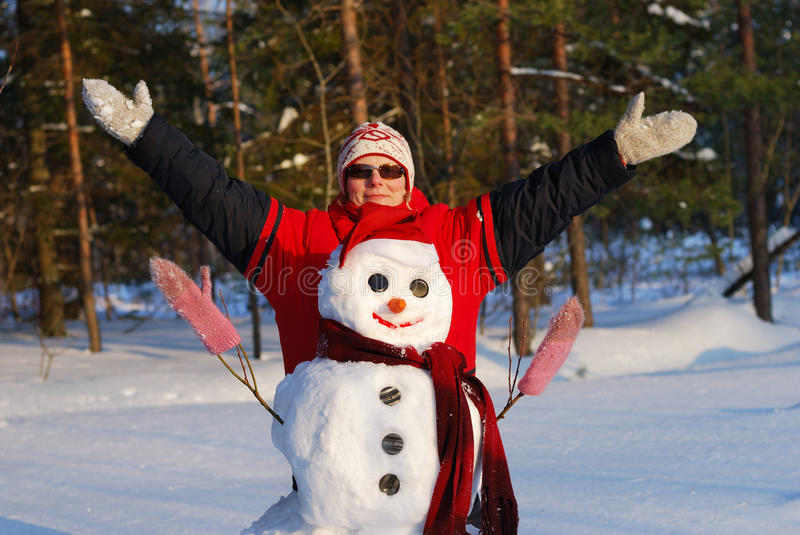 Woman poses with snowman royalty free stock photo