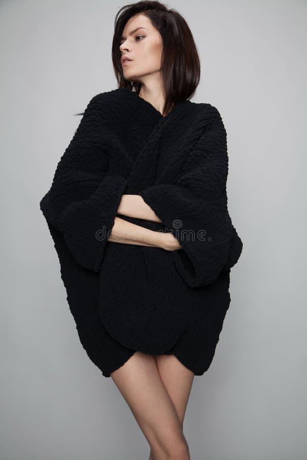 Woman posing in black long sweater stock photo
