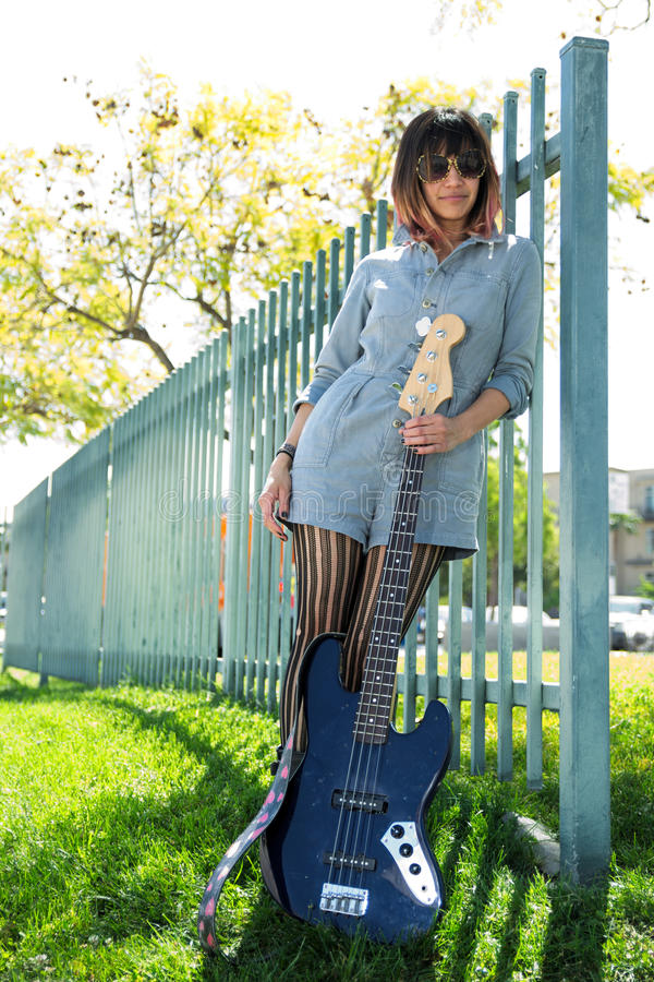 Woman posing with blue bass guitar outside stock photography