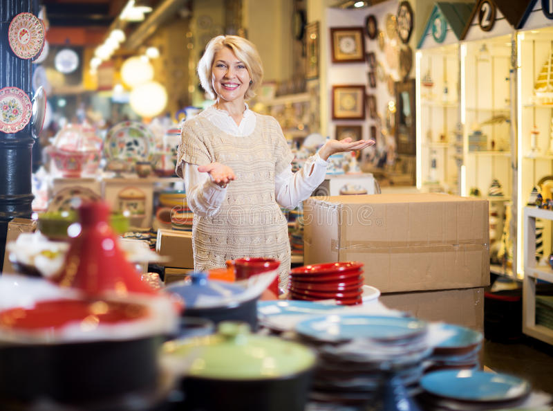 Woman posing with ceramic tableware. Cheerful mature woman posing with ceramic tableware on the market royalty free stock photography