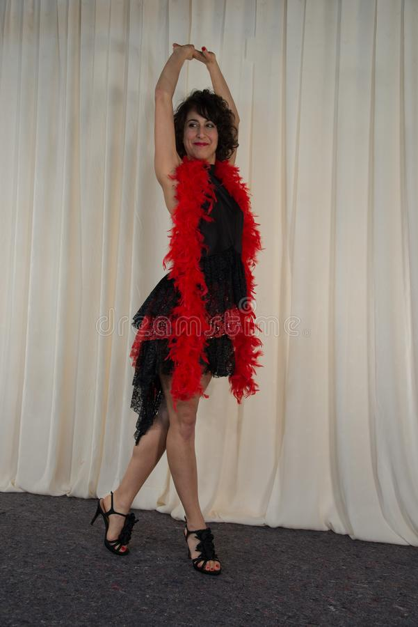 Woman posing with dancing costume, with red feather boa stock image